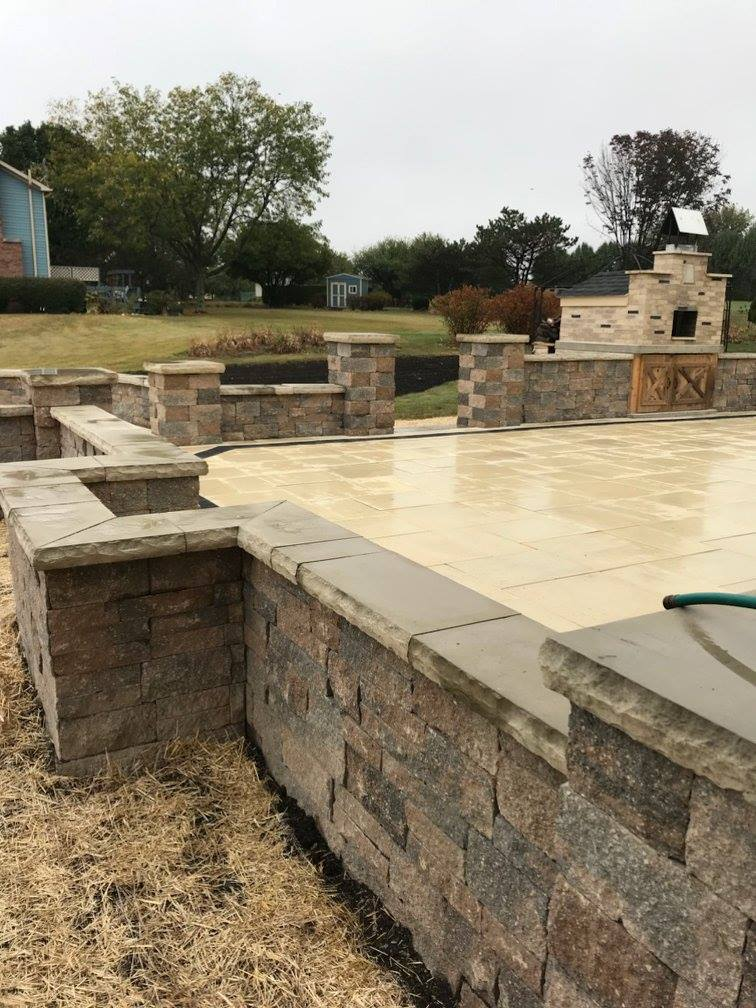 Tan brick paver patio with walls and fireplace design project.