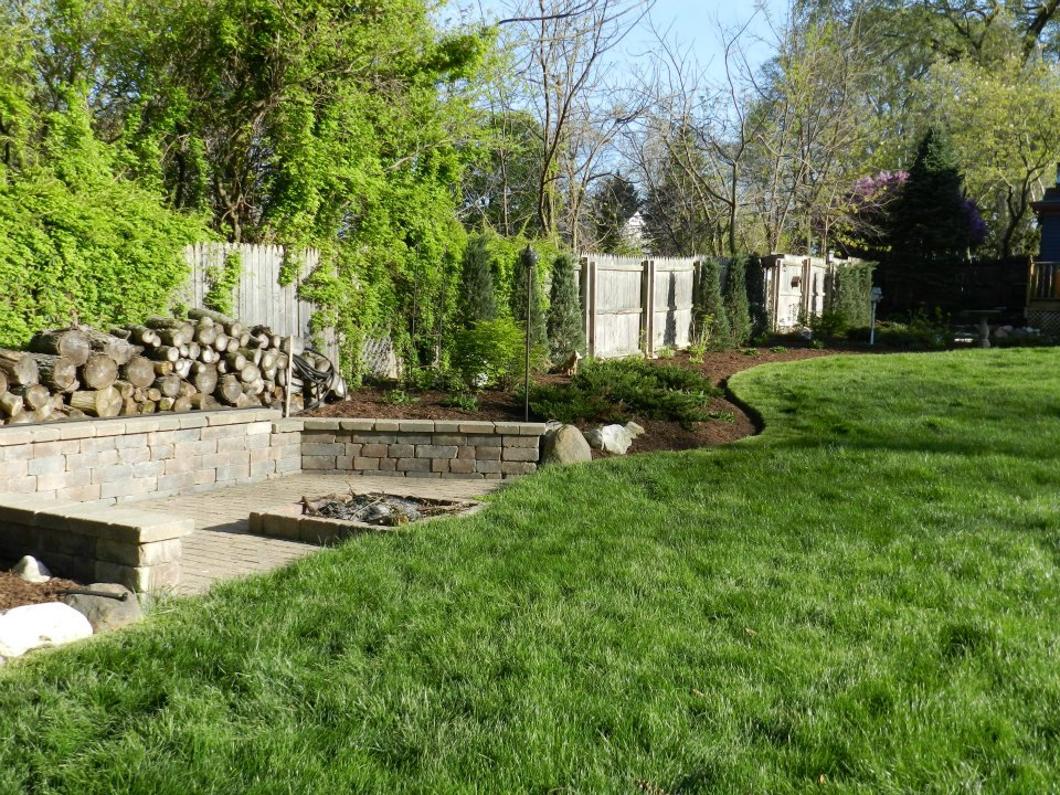 Brick Fire pit with edged mulch beds and greenery design project
